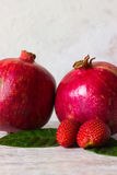 Pomegranate and strawberry. Fruits and berries on a light background Royalty Free Stock Images
