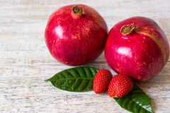 Pomegranate and strawberry on a light tree. Fruits and berries on a light background Royalty Free Stock Photos