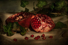 Pomegranate on table. Fresh juicy red pomegranate with leafs on table royalty free stock photography