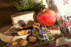 Pomegranate, walnuts and Christmas gifts among the flowers Royalty Free Stock Images