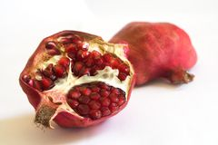 Pomegranate on a white background. Close-up of a pomegranate cut in two pieces; on a white background; in perspective Stock Photo