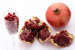 Pomegranate, whole and broken-up. Ripe pomegranates, Punica granatum, broken open and whole. Seeds of this fruit in a champagne glass Stock Photos