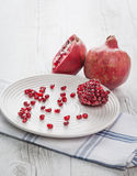 Pomegranate whole, half and seeds on plate Royalty Free Stock Image