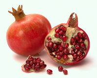 Pomegranate whole and open-face with seeds Royalty Free Stock Photo