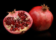 Pomegranate whole and open-face with seeds Royalty Free Stock Image