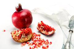 Pomegranate whole and pieces with grains on a white plate Royalty Free Stock Images