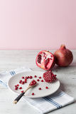 Pomegranate whole and seeds with wooden spoon on table. Vertica Royalty Free Stock Photos