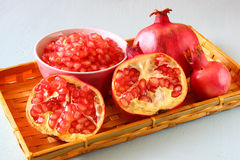 Pomegranate on wooden table, and fresh pomegrante seed in bowl - top view. Stock Photos