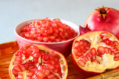 Pomegranate on wooden table, and fresh pomegrante seed in bowl - top view. Royalty Free Stock Images