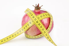 Pomegranate and yellow measuring tape. On a white background Stock Photos