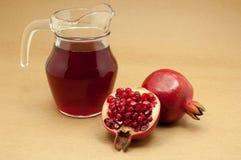Pomegranatefruktsaft i en tillbringare och en mogen pomegranate Fotografering för Bildbyråer