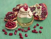 Pomegranaten kärnar ur olja buteljerar in på blåttträbakgrund Royaltyfri Fotografi