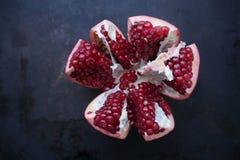 Pomegranateon rojo, maduro cortado un fondo oscuro, jugo de la granada, las propiedades beneficiosas de la granada imagen de archivo
