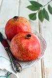 Pomegranates. Whole pomegranates on a white plate Royalty Free Stock Photography