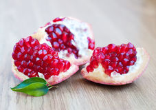 Pomegranates. Pomegranate with leaf on a wood background royalty free stock image