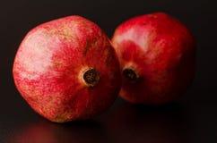 Pomegranates. Two ripe red pomegranates against a dark background royalty free stock photo