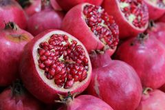 Half Pomegranates with seeds at the market stall background Royalty Free Stock Image