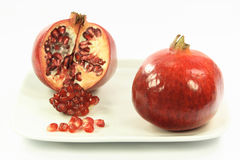 Pomegranates over white. Picture of entire and cut pomegranates with single seeds and a cluster of seeds over white background Royalty Free Stock Images