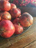 Pomegranates in the plate on the wooden floor. Background  light shine flower basket Royalty Free Stock Images