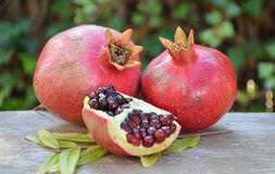 Pomegranates. Ripe pomegranates with open piece with leaf on the rustic surface Royalty Free Stock Image