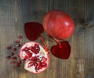 Pomegranates with ruby red beans in love with two hearts on wooden table background, selective focus, rustic style. Valentine`s stock photos