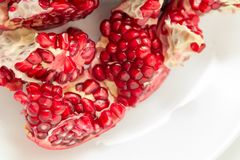 Pomegranates, sliced, pithy fruit, pomegranate seeds,. Pomegranate on white background, red, spine on top, six corners Stock Images