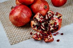 pomegranates on the table on a gray napkin on a linen tablecloth royalty free stock photo