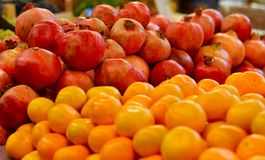 Pomegranates and tangerines at outdoor market stock images