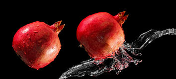 Pomegranates and water stream Stock Photography