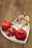 Pomegranates and a wooden heart Royalty Free Stock Photo