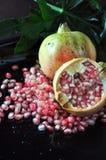 Pomegrannate cor-de-rosa espalhado no fundo preto Imagem de Stock