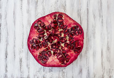 Pomegranate. Section overhead view on a white wooden kitchen table Royalty Free Stock Photo
