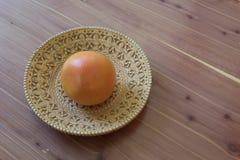 Pomelo anaranjado y rosado grande en un cuenco de la corteza de abedul en una tabla de madera, espacio de la copia Foto de archivo