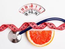 Pomelo con la cinta métrica en escala del peso dieting Fotografía de archivo libre de regalías
