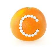 Pomelo con las píldoras de la vitamina C sobre el backgro blanco Fotografía de archivo