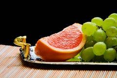 Pomelo cortado y uvas listos para ser servidor Imagen de archivo