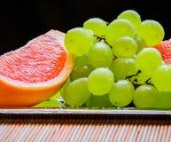 Pomelo cortado y uvas listos para ser servidor Imagen de archivo libre de regalías