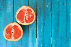 Pomelo jugoso de la fruta cítrica en un fondo azul foto de archivo