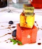 Pomelo, kiwi y postre anaranjado con la salsa de chocolate Foto de archivo