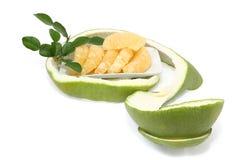Pomelo maduro en el plato blanco con la cáscara verde en el fondo blanco Imágenes de archivo libres de regalías