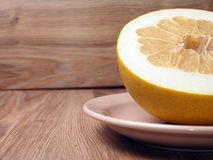 Pomelo on a plate. Pomelo the fruit cut on a plate Royalty Free Stock Images
