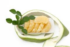 Pomelo puesto en una placa blanca con las hojas y la cáscara del verde en blanco Fotografía de archivo