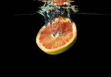 Pomelo que cae en el agua Fotos de archivo libres de regalías