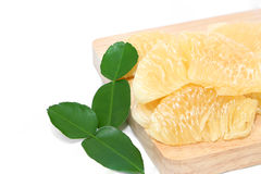 Pomelo ripe laying on a wooden cutting board white background Royalty Free Stock Images