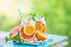 Pomelo y agua anaranjada en los tarros de cristal en el aire abierto Imágenes de archivo libres de regalías