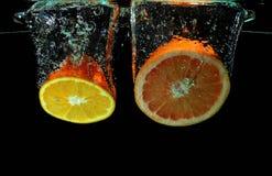Pomelo y el caer anaranjada en el agua Imagen de archivo libre de regalías