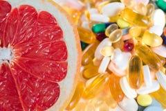 Pomelo y píldoras, suplementos de la vitamina en el fondo blanco, concepto de la dieta sana Imagenes de archivo