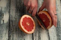 pomelos del corte de la mujer en un tablero de madera, tiro del estudio Imagen de archivo libre de regalías