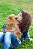 Pomeranian licking a young woman Royalty Free Stock Images