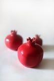 Pomergranates rouges en céramique sur le fond blanc Photographie stock